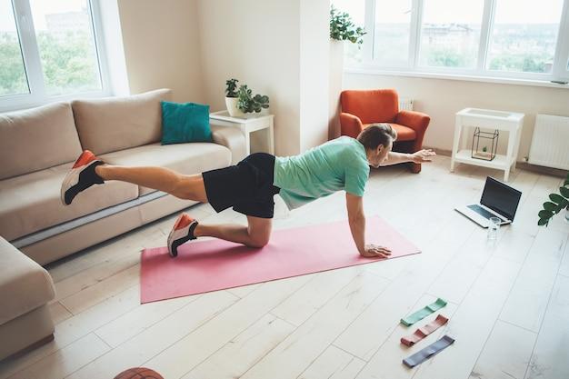 Bovenaanzicht foto van een blanke man die zich uitstrekt over de vloer, het dragen van sportkleding en met behulp van een laptop