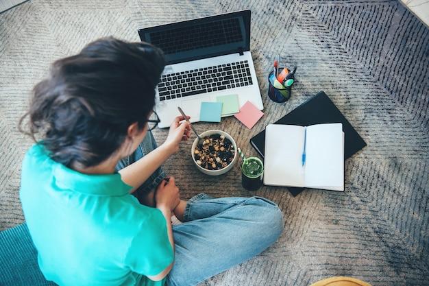 Bovenaanzicht foto van een blanke vrouw granen eten en huiswerk thuis op de vloer