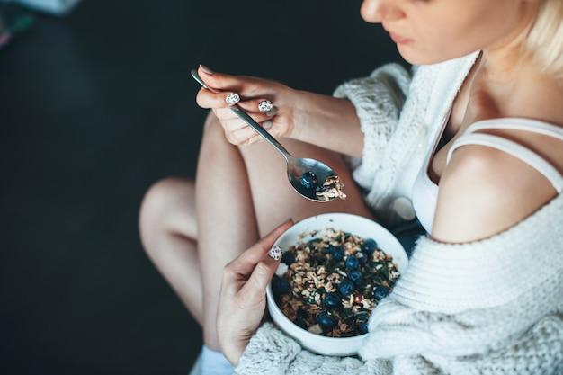 Bovenaanzicht foto van een blanke vrouw in een gebreide trui thuis granen met bessen eten