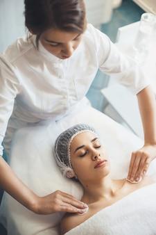 Bovenaanzicht foto van een blanke vrouw met medische pet liggend in een spa salon