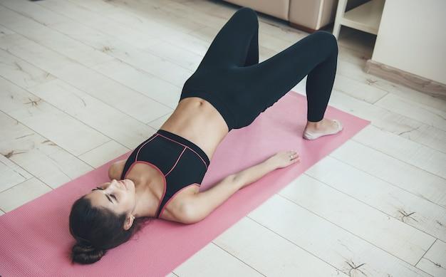 Bovenaanzicht foto van een blanke vrouw planking thuis op een roze tapijt in sportkleding