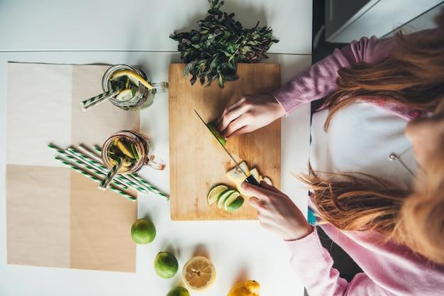 Bovenaanzicht foto van een gember vrouw een citroen snijden terwijl het maken van verse mojito thuis