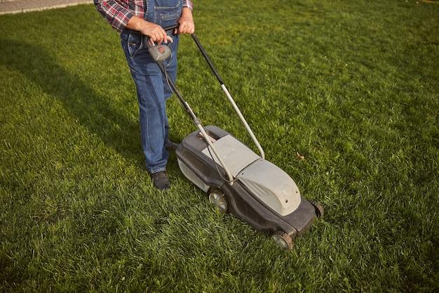 Bovenaanzicht foto van een verantwoordelijke tuinman die een groen gazon maait met een grasmaaier