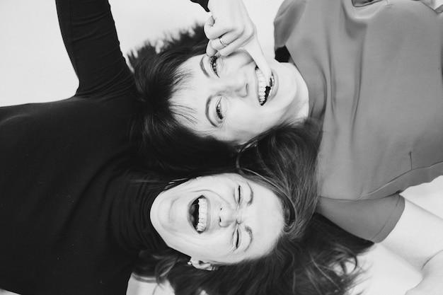 Bovenaanzicht foto van gelukkige vriendinnen ontspannen head-to-head terwijl ze blij glimlachen. vriendschap concept