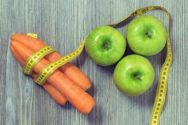 Bovenaanzicht foto van groene appels wortelen en meetlint op houten tafel achtergrond