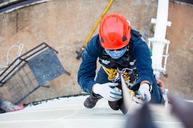 Bovenaanzicht foto van industriële lasser met touwtoegang die op hoogte werkt met een harnas, helm veiligheidsuitrusting touwtoegangsinspectie van de industrie van de dikteopslagtank.