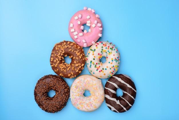 Bovenaanzicht foto van piramide van donuts geïsoleerd blauwe achtergrond