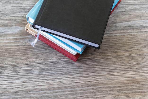 Bovenaanzicht foto van stapel boeken op geïsoleerde houten tafel achtergrond