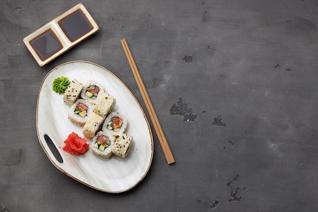 Bovenaanzicht foto van sushi roll met sesam op donkergrijze achtergrond