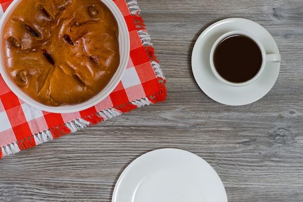 Bovenaanzicht foto van taart kopje drinken en lege plaat op houten tafel