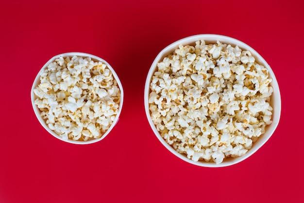 Bovenaanzicht foto van twee dozen met popcorn geïsoleerde rode achtergrond