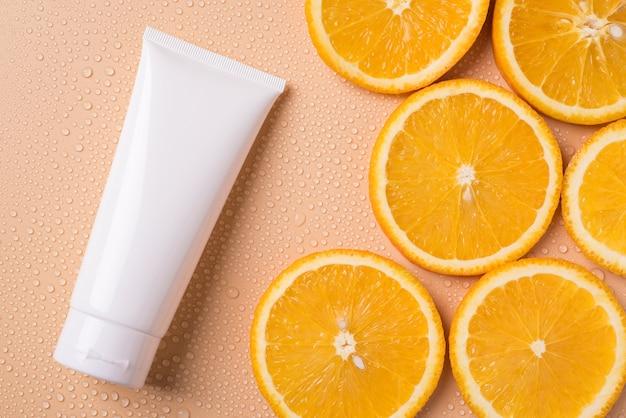 Bovenaanzicht foto van witte buis en stukjes sinaasappel
