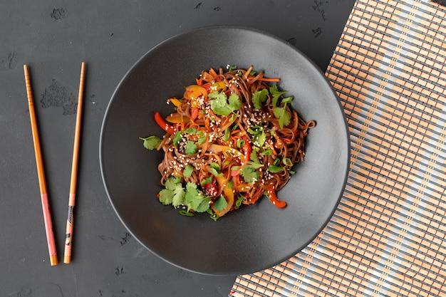 Bovenaanzicht foto van wok noedels met groenten en vlees in kom op grijze achtergrond