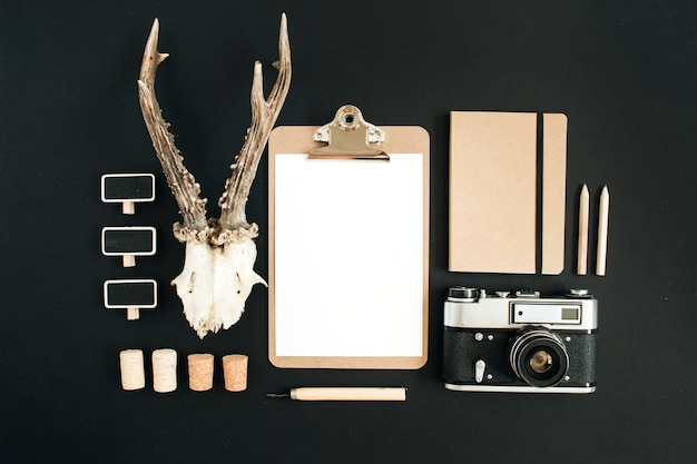 Bovenaanzicht fotograaf concept. retro camera, geitenhoorns, klembord, ambachtelijk dagboek op zwarte schoolbordachtergrond.