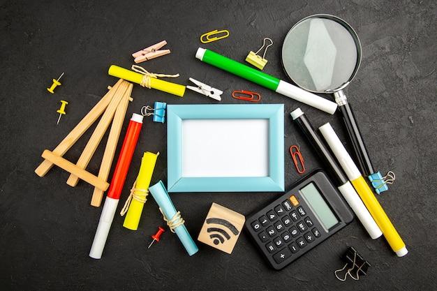 Bovenaanzicht fotolijst met kleurrijke potloden op donkere oppervlakte kunst kleur tekening college voorbeeldenboek school notitieblok