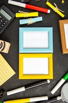 Bovenaanzicht fotolijsten met kleurrijke potloden op een donkere ondergrond kunst kleur tekening notitieblok pen college schrift school