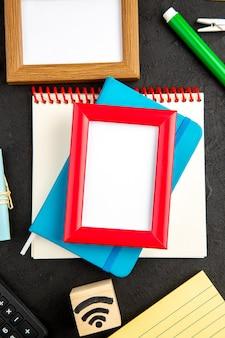 Bovenaanzicht fotolijsten met notitie en kleurrijke potloden op donkere achtergrond kleur tekening school notitieblok pen college kunst voorbeeldenboek