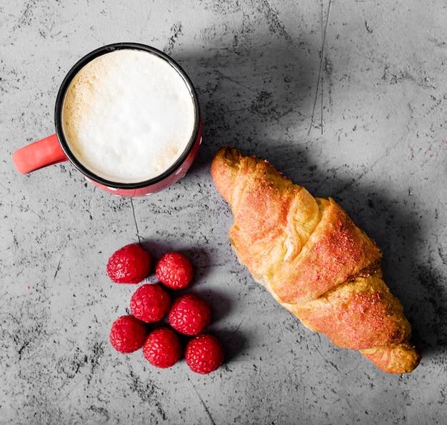 Bovenaanzicht frambozen en croissant