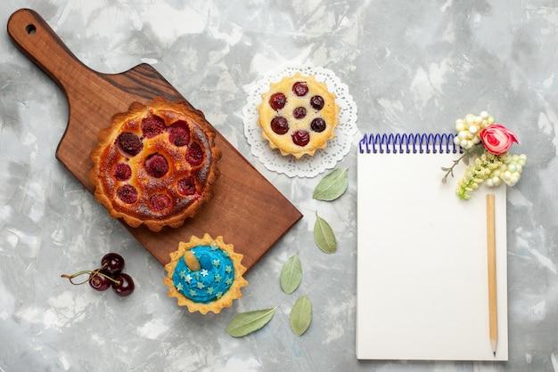 Bovenaanzicht frambozencake met kleine cake samen met kladblok op de lichte tafel taart taart kersen fruit zoet