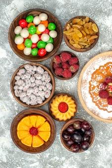 Bovenaanzicht frambozencake met snoepjes en rozijnen op witte oppervlaktevruchten biscuittaarttaart