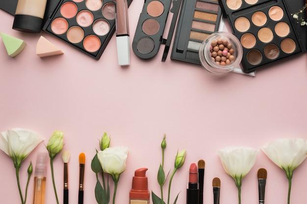 Bovenaanzicht frame met bloemen en lippenstiften