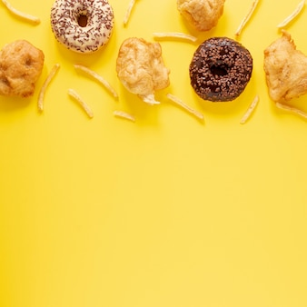 Bovenaanzicht frame met donuts en gele achtergrond