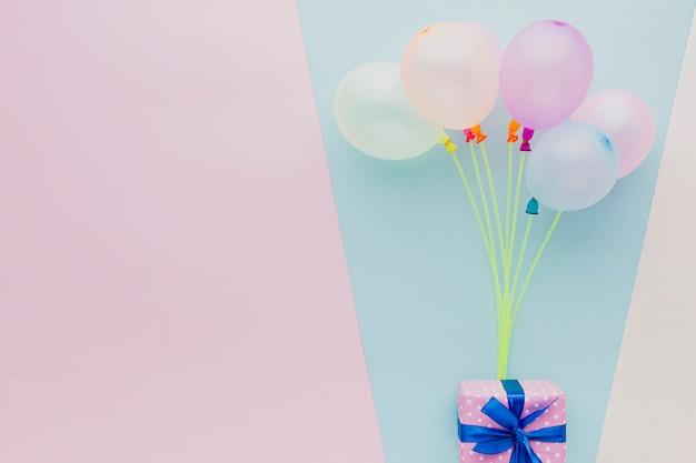 Bovenaanzicht frame met kleurrijke ballonnen en cadeau