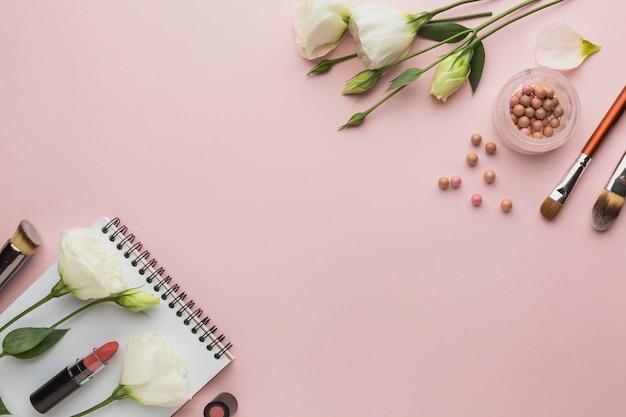 Bovenaanzicht frame met make-up producten en bloemen