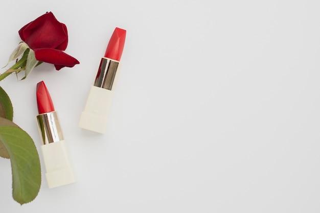 Bovenaanzicht frame met rode lippenstiften en roos