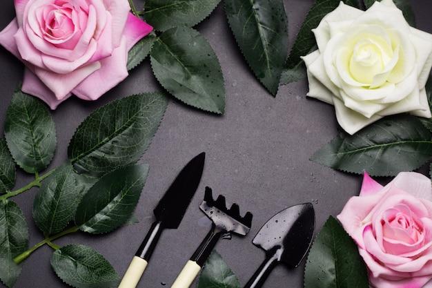 Bovenaanzicht frame van tuingereedschap, rozenblaadjes, roze bloemen.