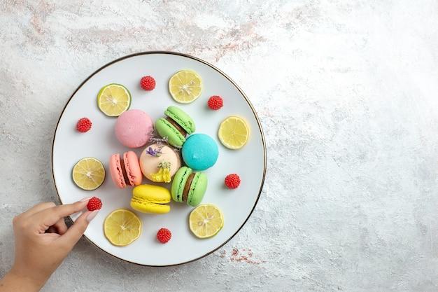 Bovenaanzicht franse macarons heerlijke kleine cakes met schijfjes citroen op witte ruimte
