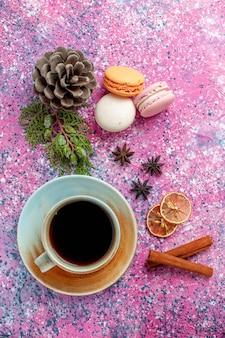 Bovenaanzicht franse macarons heerlijke kleine cakes met thee op roze oppervlak