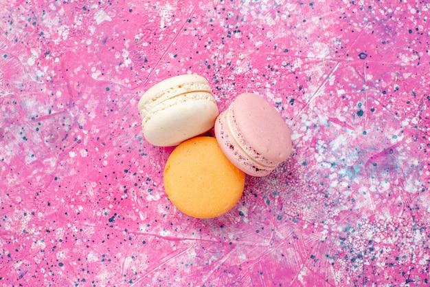 Bovenaanzicht franse macarons heerlijke kleine cakes op het roze bureau bak cake zoete suikertaart confituur
