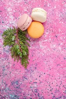 Bovenaanzicht franse macarons heerlijke kleine cakes op roze oppervlak