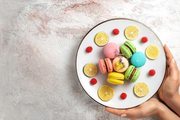 Bovenaanzicht franse macarons kleine heerlijke taarten met schijfjes citroen op licht-wit oppervlak cake koekje suiker koekje zoet