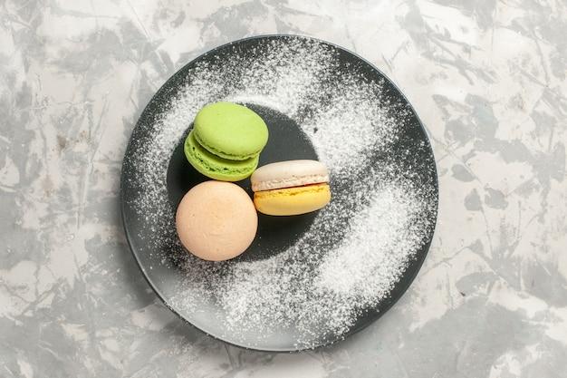 Bovenaanzicht franse macarons kleine heerlijke taarten op wit oppervlak koekje suiker cake zoete taart thee koekje