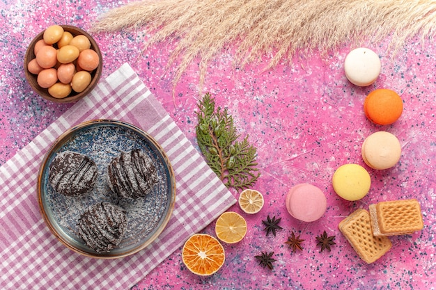 Bovenaanzicht franse macarons met chocoladetaart op lichtroze