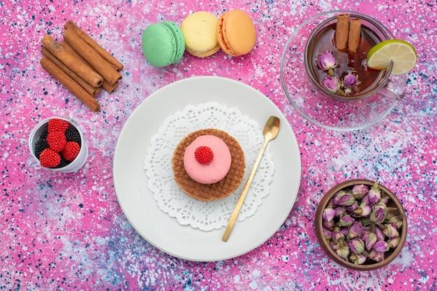 Bovenaanzicht franse macarons met kaneel bessen en thee op de kleurrijke achtergrond cake koekje suiker zoete kleur bakken