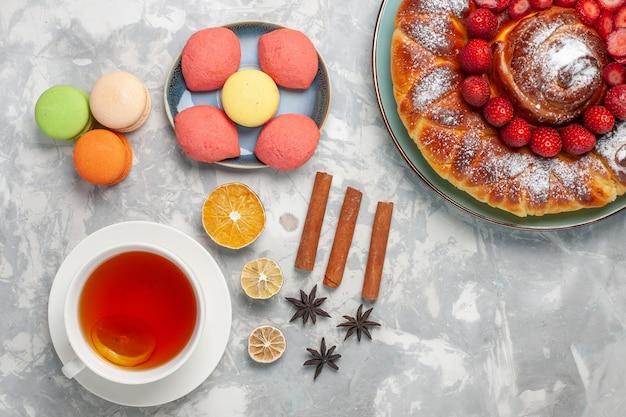 Bovenaanzicht franse macarons met kleine cakes, aardbeientaart en kopje thee op witte ondergrond cake koekje suiker zoete taart thee