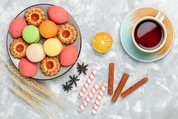 Bovenaanzicht franse macarons met koekjes, kaneel en thee op lichtwit oppervlak