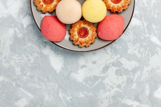 Bovenaanzicht franse macarons met koekjes op licht wit oppervlak