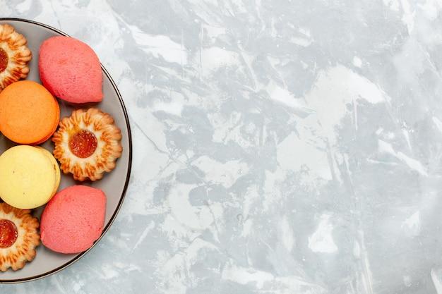 Bovenaanzicht franse macarons met koekjes op lichtwit bureau