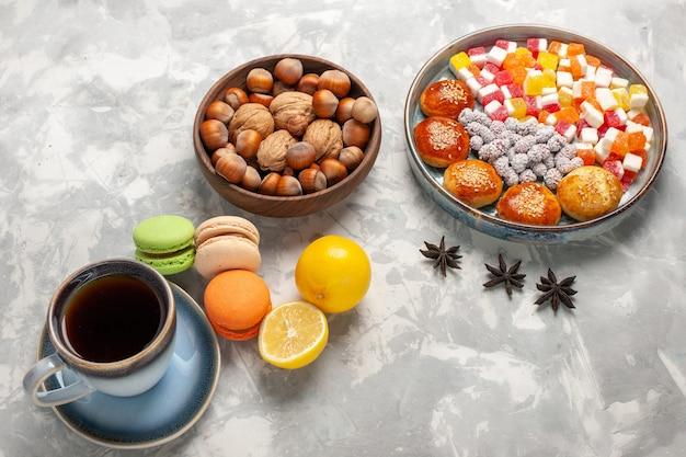 Bovenaanzicht franse macarons met kopje thee noten en gebak op witte ondergrond