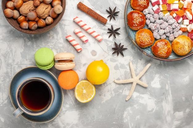 Bovenaanzicht franse macarons met kopje thee op lichte witte ondergrond