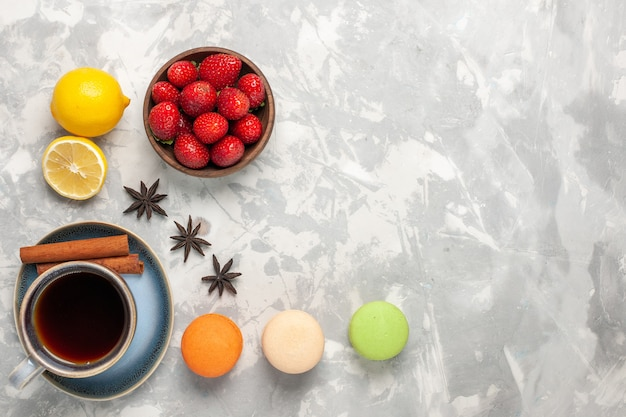 Bovenaanzicht franse macarons met thee en verse aardbeien op witte ondergrond