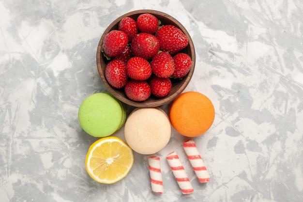Bovenaanzicht franse macarons met verse rode aardbeien op witte ondergrond