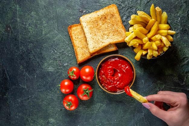 Bovenaanzicht frietjes eten met ketchup door vrouwtje op donkere ondergrond