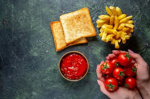 Bovenaanzicht frietjes met toast en rode kerstomaatjes in vrouwelijke handen op donkere ondergrond