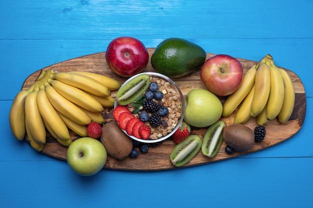 Bovenaanzicht fruit, bananen, appels, mango's, kiwi, aardbeien, bosbessen, met ontbijtgranen