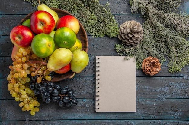 Bovenaanzicht fruit en takken witte en zwarte druiven limoenen peren appels in kom naast vuren takken grijs notitieboekje en kegels op grijze ondergrond